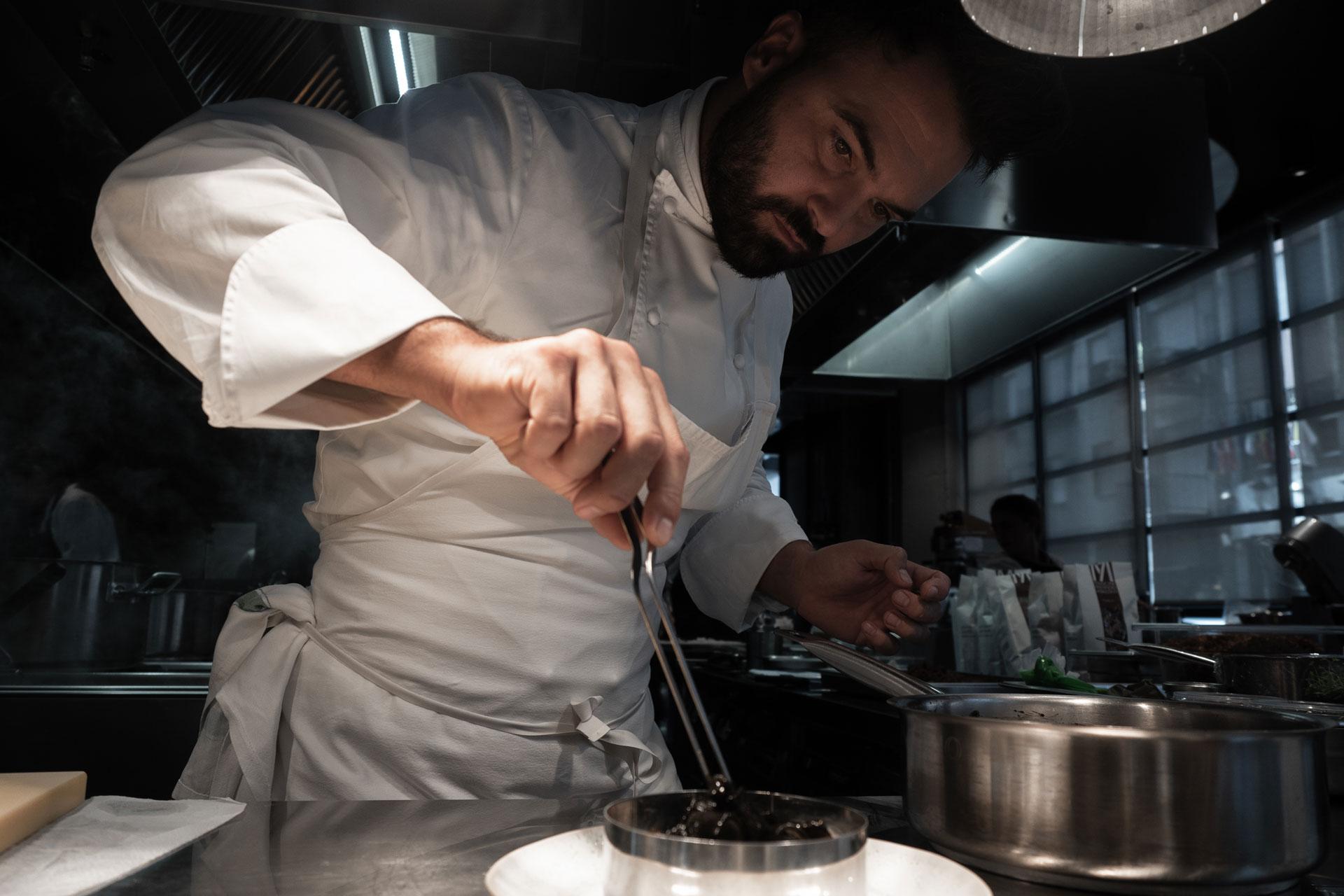 Chef Enrico Croatti impiatta nella cucina del ristorante Moebius Milano